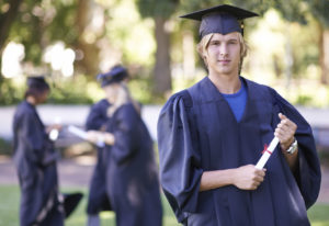 Portrait of a smiling graduate holding his diploma with her former graduates in the background