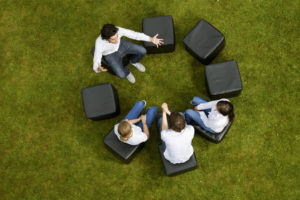 People talking in circle in grass